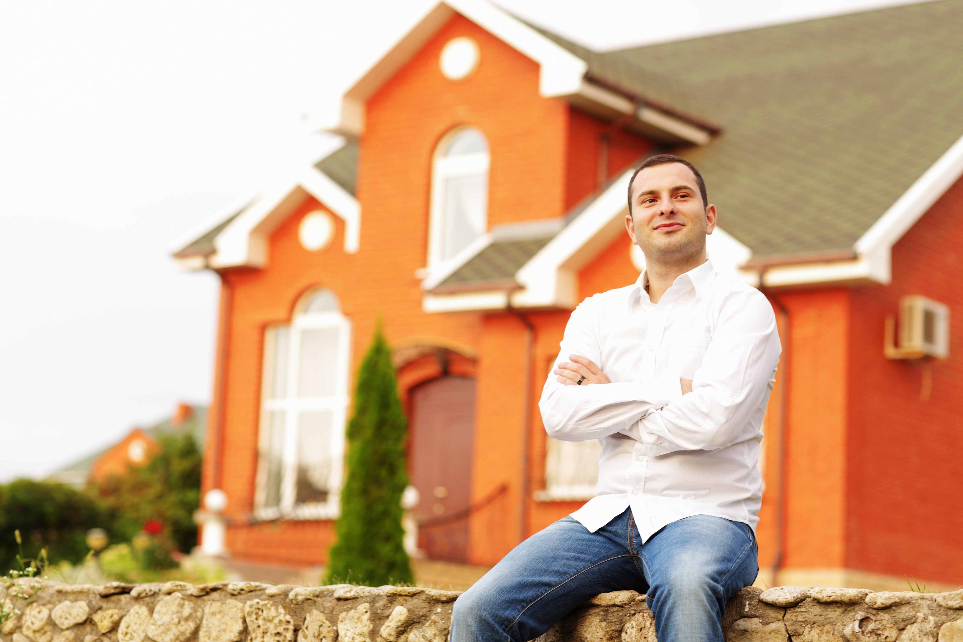 Happy man sitting in front of an orange-bricked house.|Source: Shutterstock