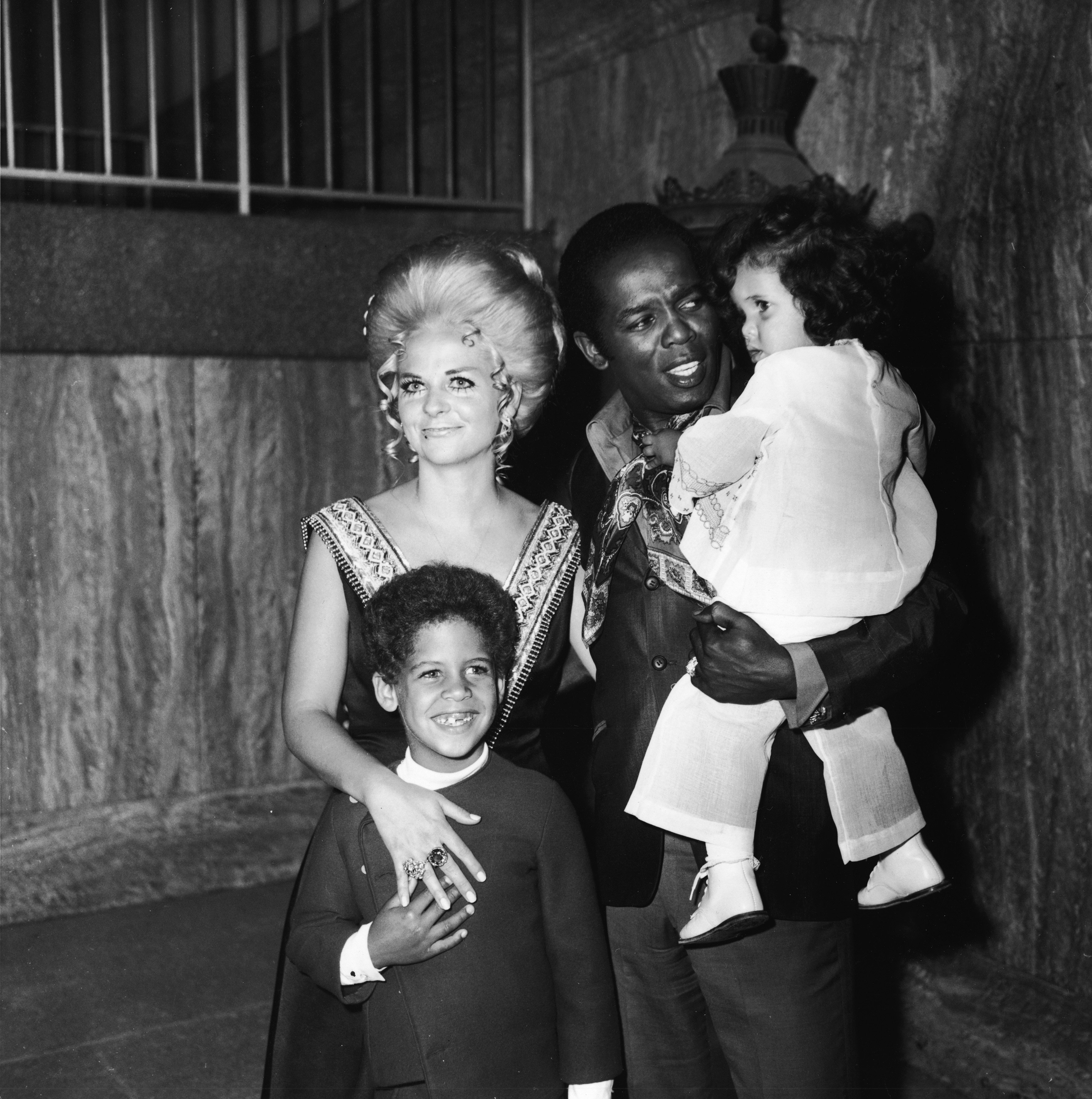 Lou Rawls holds his daughter Louanna as his wife Lana Jean and son Lou Jr. stand with him at the opening of his stint at the Century Plaza Hotel, Los Angeles, California, 1973. | Photo: Getty Images
