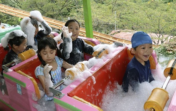 Young kids pictured in a roller coaster with built-in bathtubs filled with hot spring-water bubbles | Photo: Getty Images