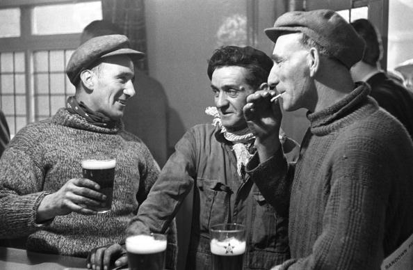 Three men having a drink in bar | Photo: Getty Images