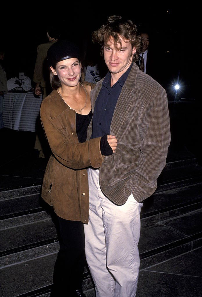 """Sandra Bullock and Tate Donovan share an embrace at the """"Wings of Change"""" Giorgio Photo Exhibit Benefit onNovember 03, 1993