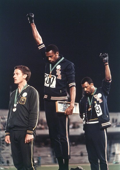 Gold medalist Tommie Smith (C) and bronze medalist John Carlos (R) of the United States raise their fists on the podium at the medal ceremony for the Athletics Men's 200m during the Mexico City Olympic Games at the Estadio Olimpico Universitario on October 14, 1968 in Mexico City, Mexico | Source: Getty Images