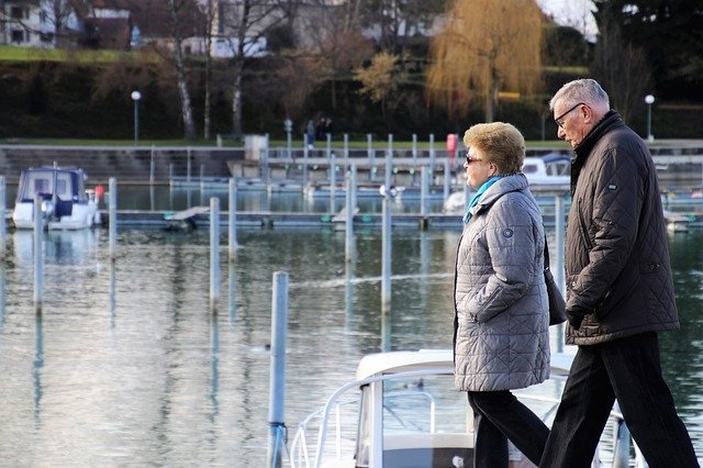 A senior couple walks along a marina | Photo: Pixabay
