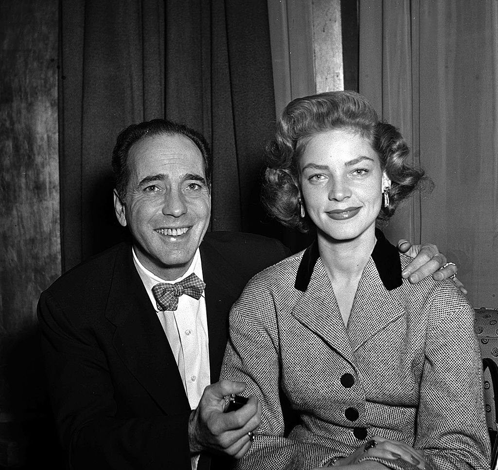 Humphrey Bogart smiles with his actress wife Lauren Bacall at a press reception at Claridges in London, 1951. | Source: Getty Images