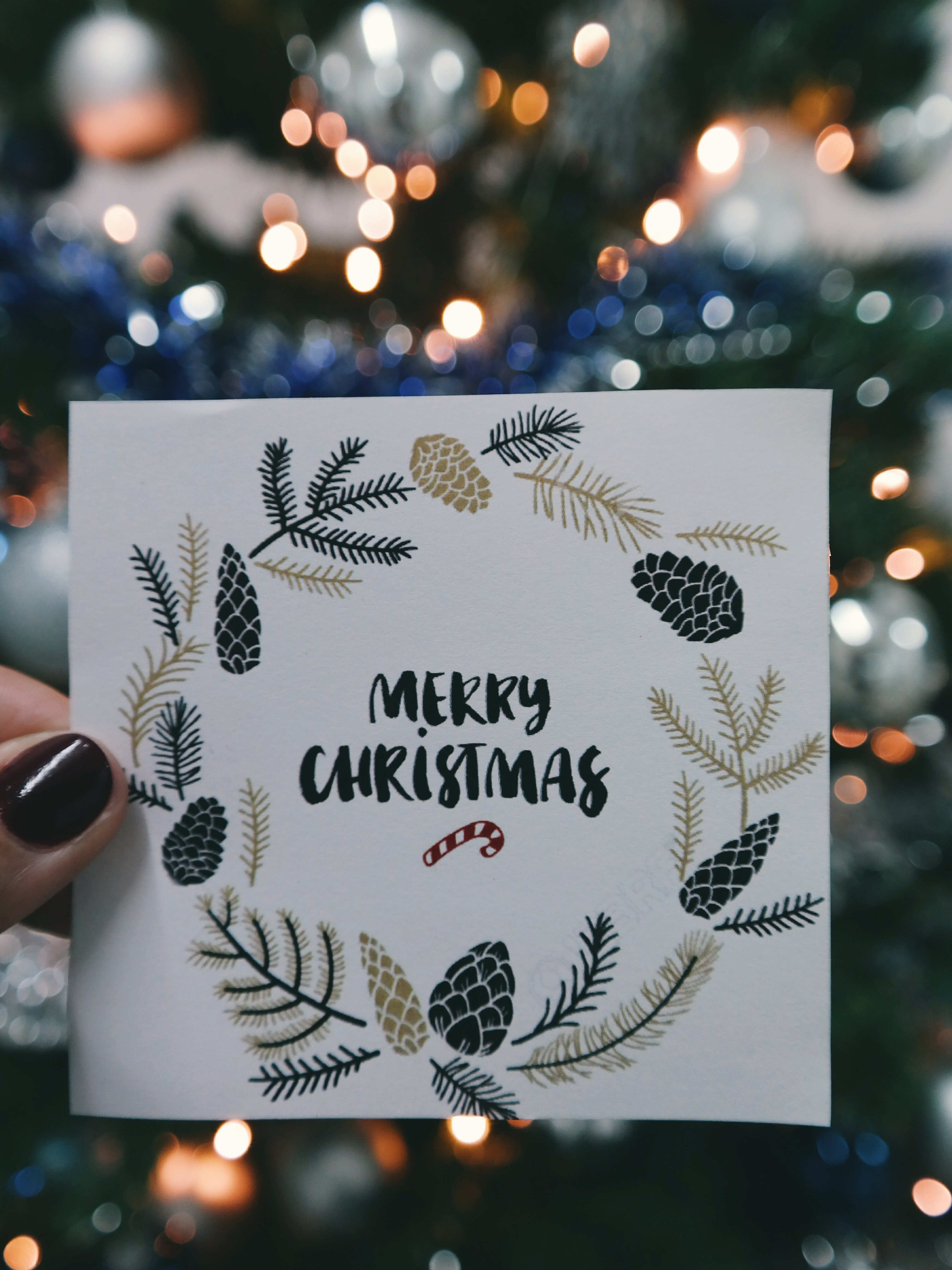 Christmas card in front of tree | Photo: Pexels.com