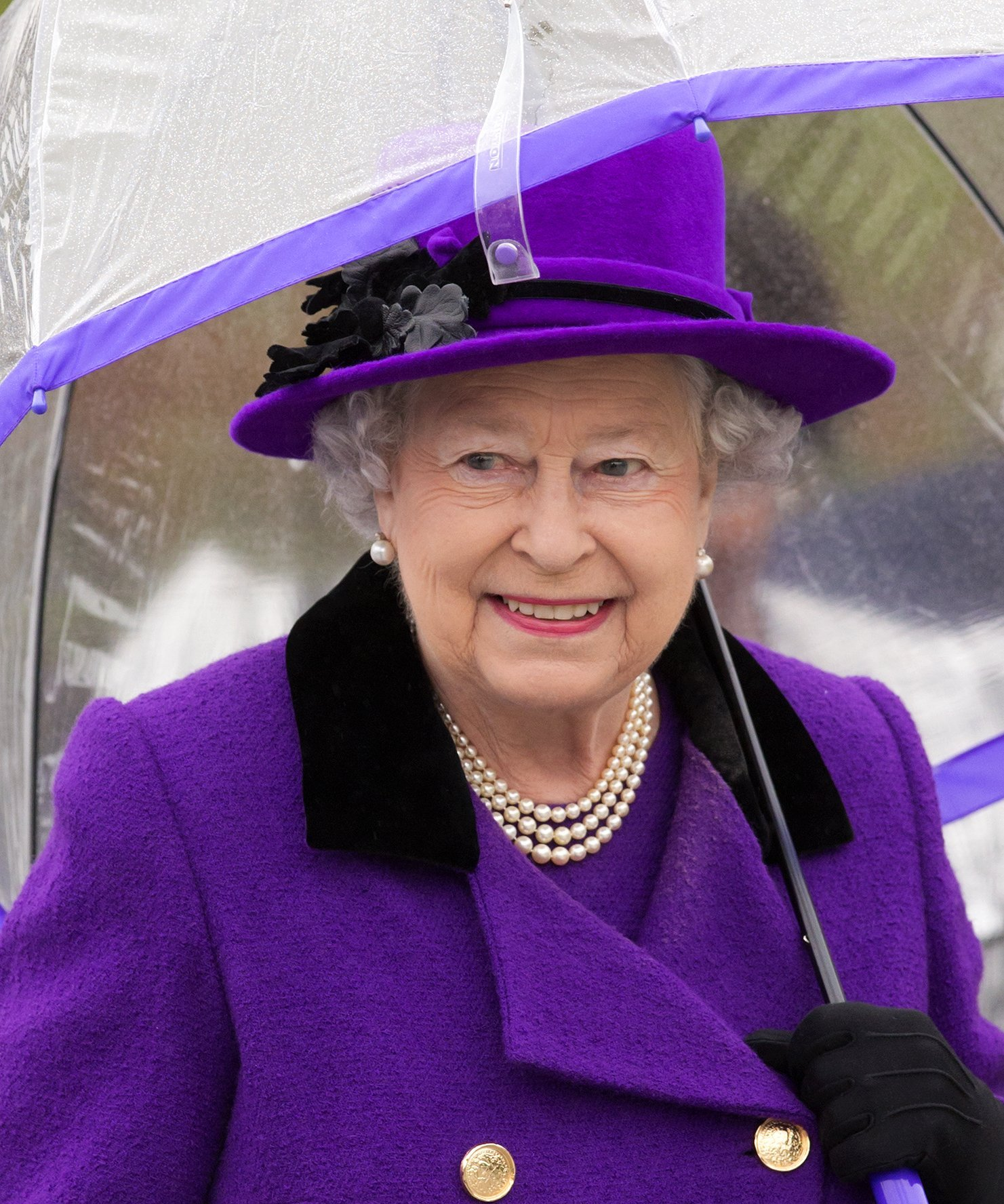 Queen Elizabeth II shelters under an umbrella as attends the opening of the newly developed Jubilee Gardens on October 25, 2012, in London, England. | Source: Getty Images.