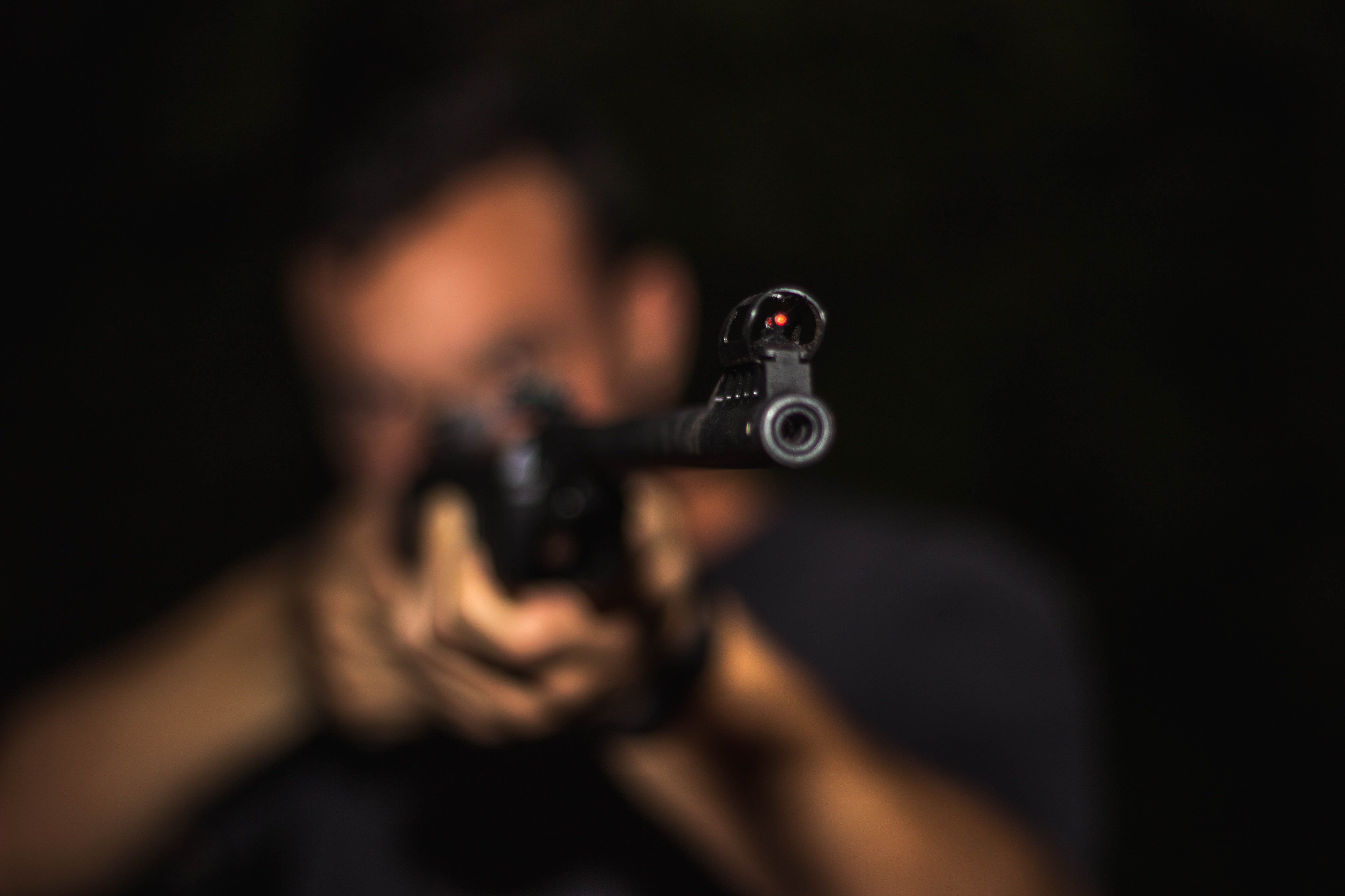 Pictured - A photo of a man holding a rifle and aiming | Source: Pexels