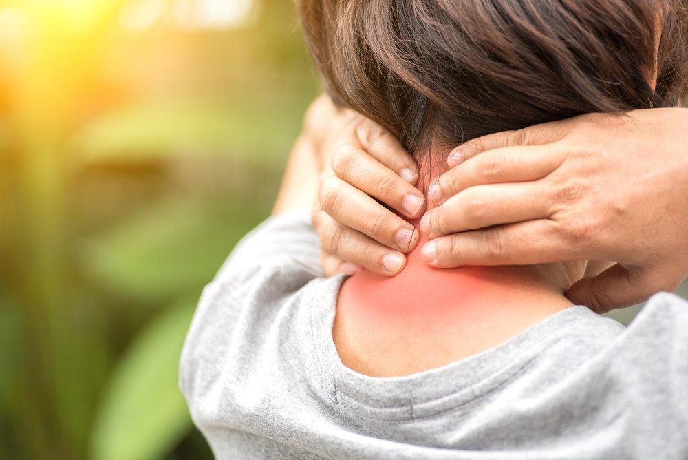 Mujer toca cuello adolorido e inflamado. Fuente: Shutterstock