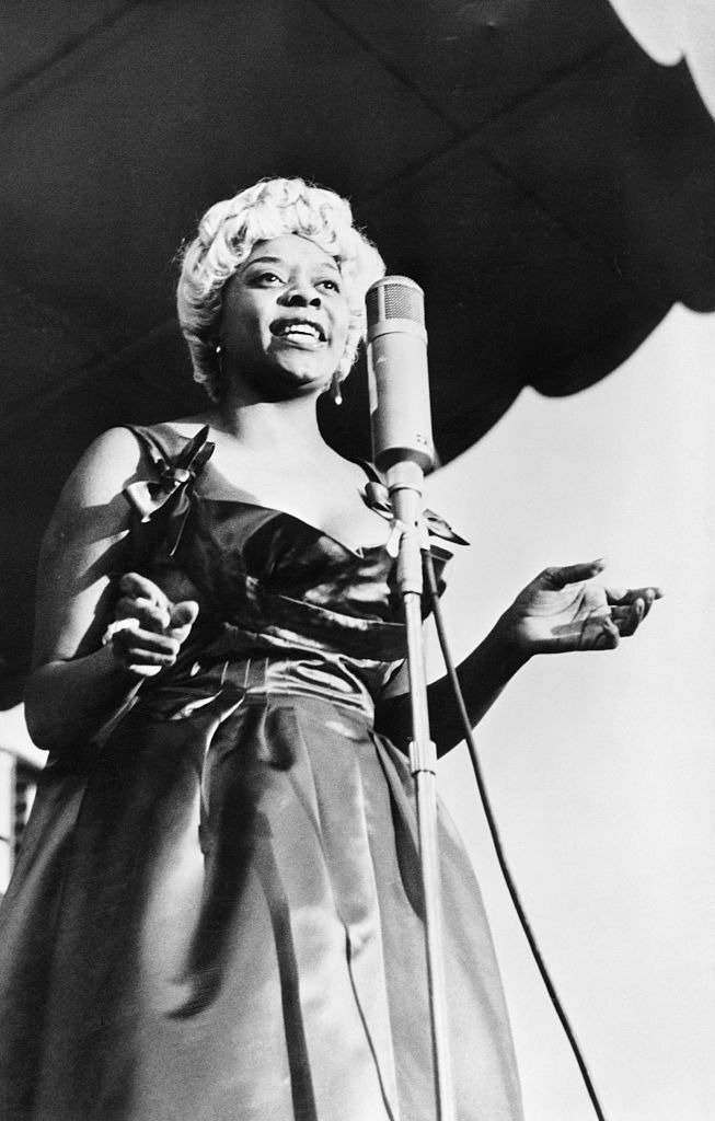 """Portrait of Dinah Washington, """"Queen of the Blues,"""" at microphone. Photograph, 1959.