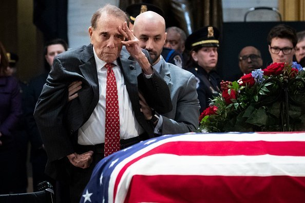 Former Senator Bob Dole stands up and salutes the casket of the late former President George H.W. Bush as he lies in state at the U.S. Capitol, December 4, 2018 in Washington, DC | Photo: Getty Images