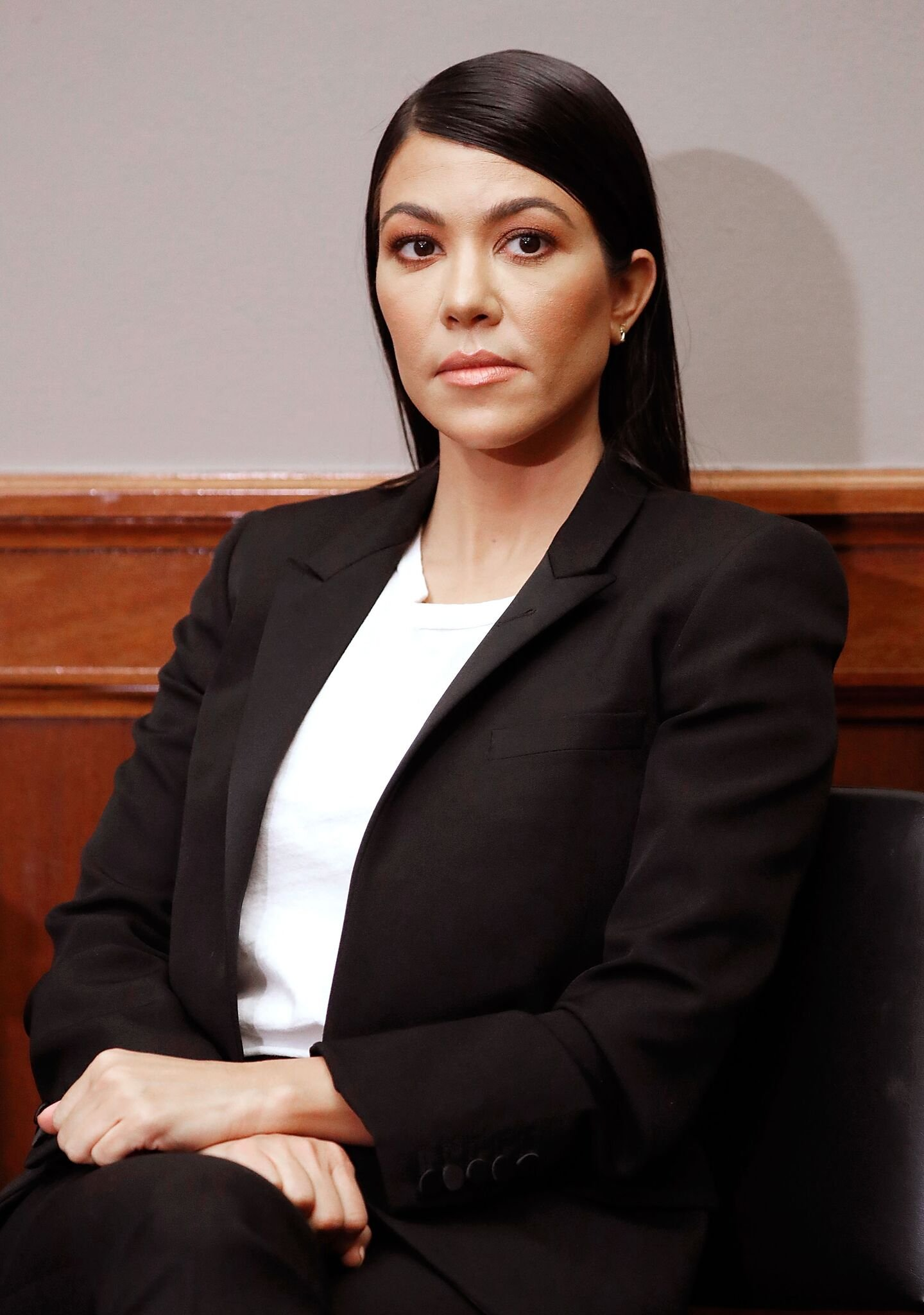 Kourtney Kardashian poses while sitting down | Getty Images