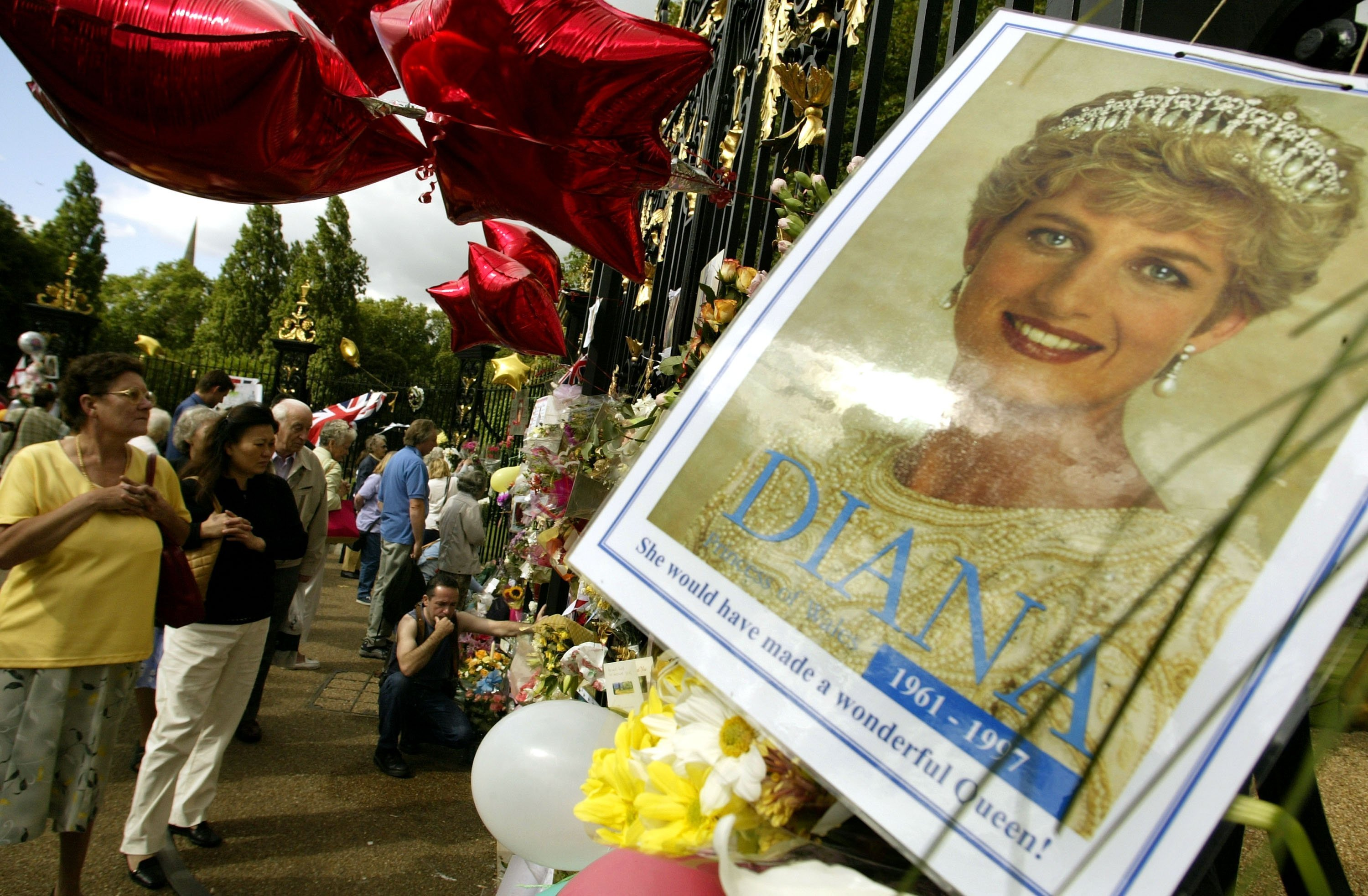 People placing flowers balloons and pictures of Princess Diana outside the gates of Kensington Palace in London, England | Photo: Getty Images