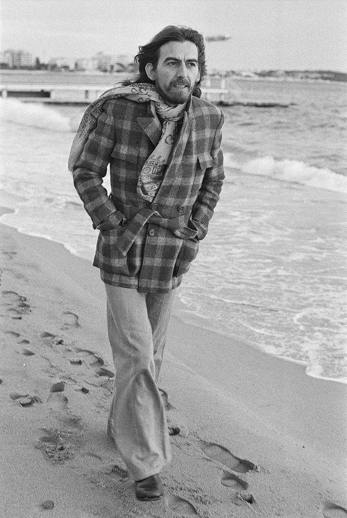 English singer-songwriter, guitarist and former Beatle, George Harrison (1943 - 2001) on the beach in Cannes, France | Getty Images / Global Images Ukraine