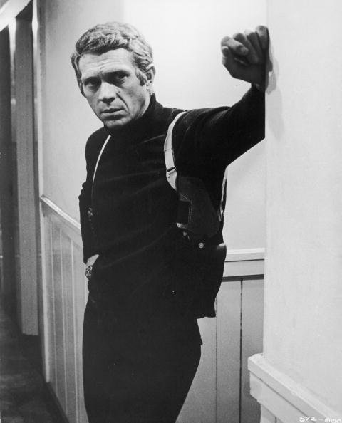 American actor Steve McQueen (1930 -1980), wearing a gun holster, leans in a hallway in a still from the film, 'Bullitt,' directed by Peter Yates, 1968 | Photo: Getty Images