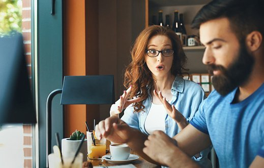 Photo of closeup side view of mid 20's couple having an argument at a coffee place | Photo: Getty Images