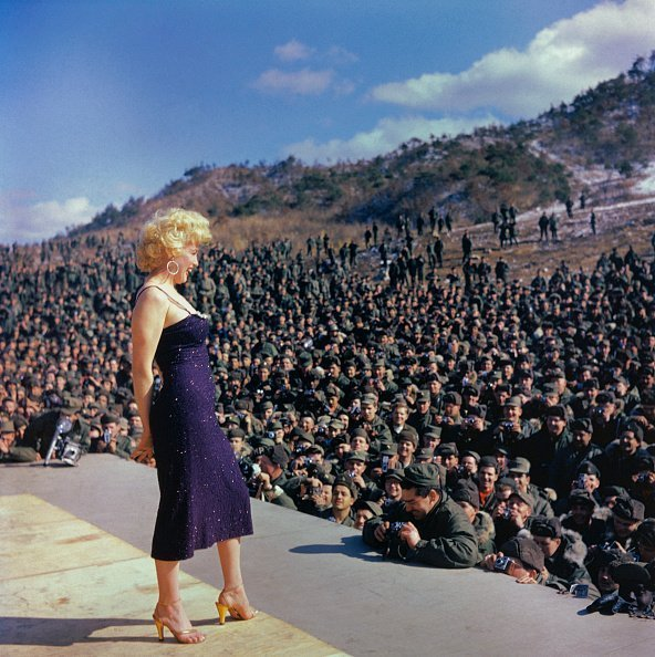 Marilyn Monroe Posing on Stage in Front of Troops as she performs in in Korea | Photo: Getty Images