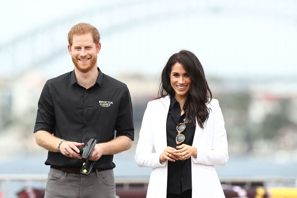 Prince Harry, Duke of Sussex and Meghan, Duchess of Sussex watch children control remote control cars during the JLR Drive Day at Cockatoo Island on October 20, 2018 | Photo: Getty Images