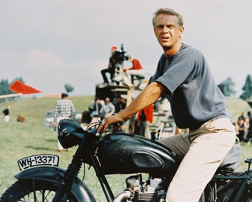 Steve McQueen sitting astride a motorcycle in a publicity image issued for the film, 'The Great Escape', in 1963. | Photo: Getty Images