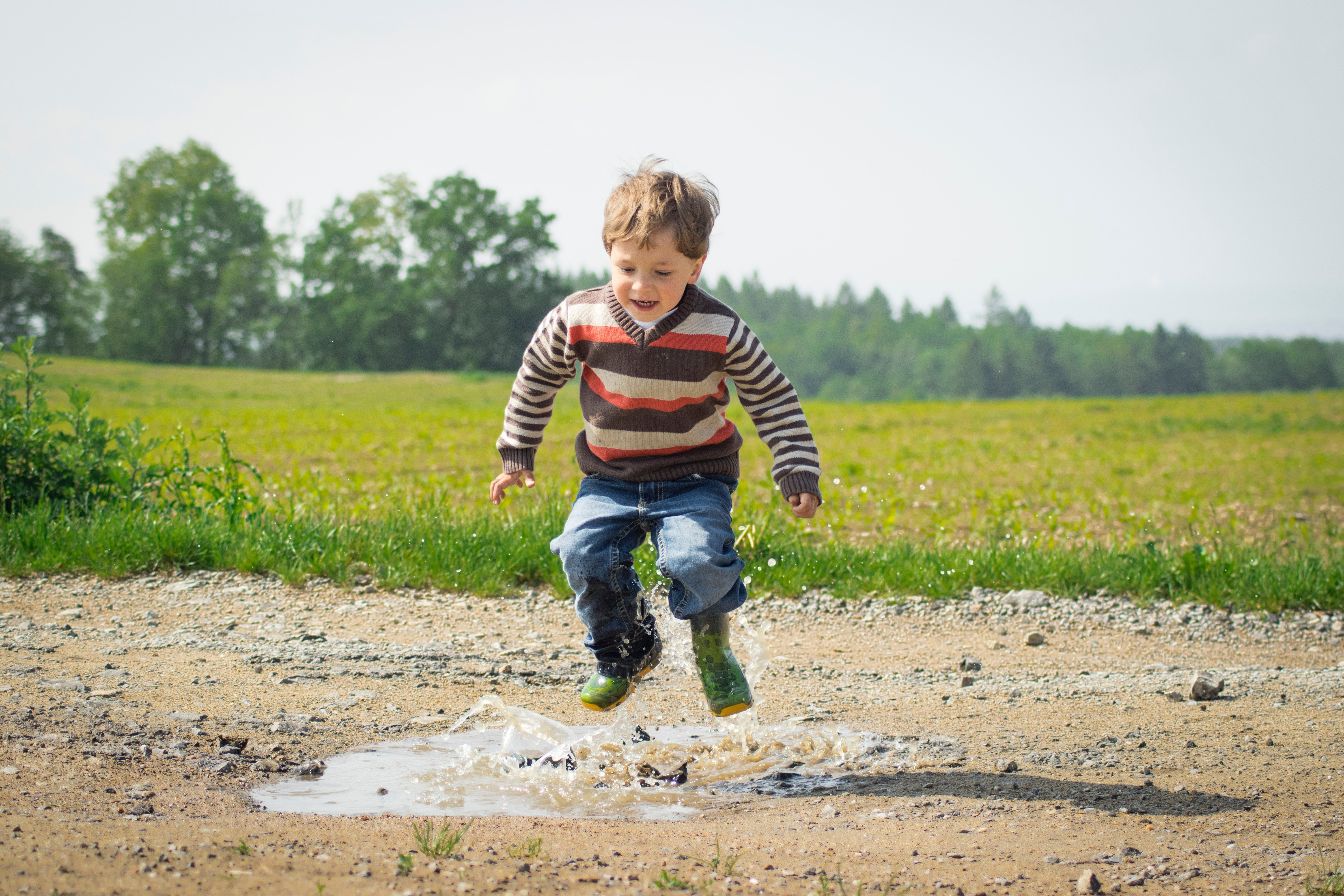 Young boy splashing in a puddle. | Source: Luna Lovegood/Pexels