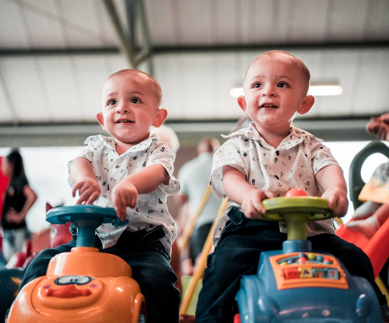 Twin babies sitting on toy cars | Source: Pexels