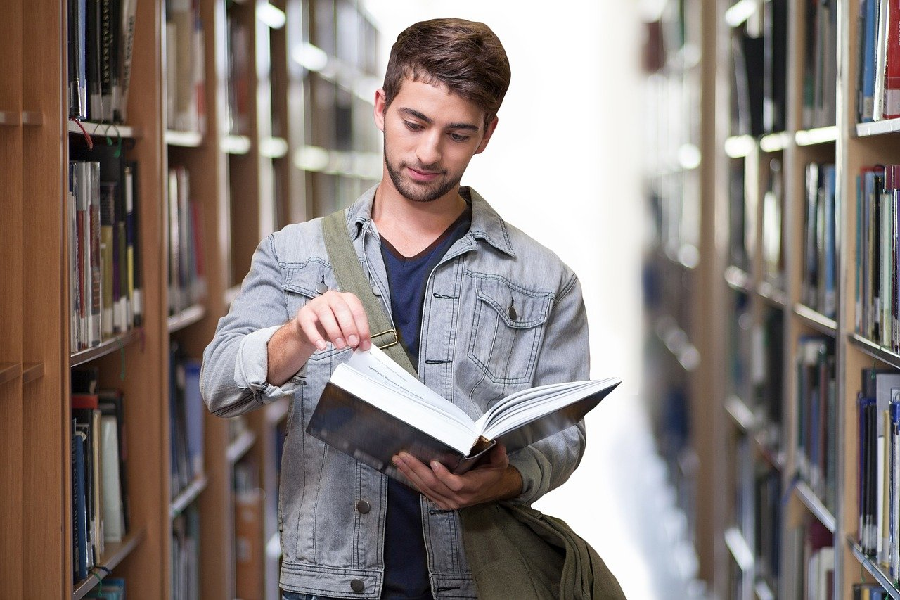 A photo of a male college student in a library. | Photo: Pixabay