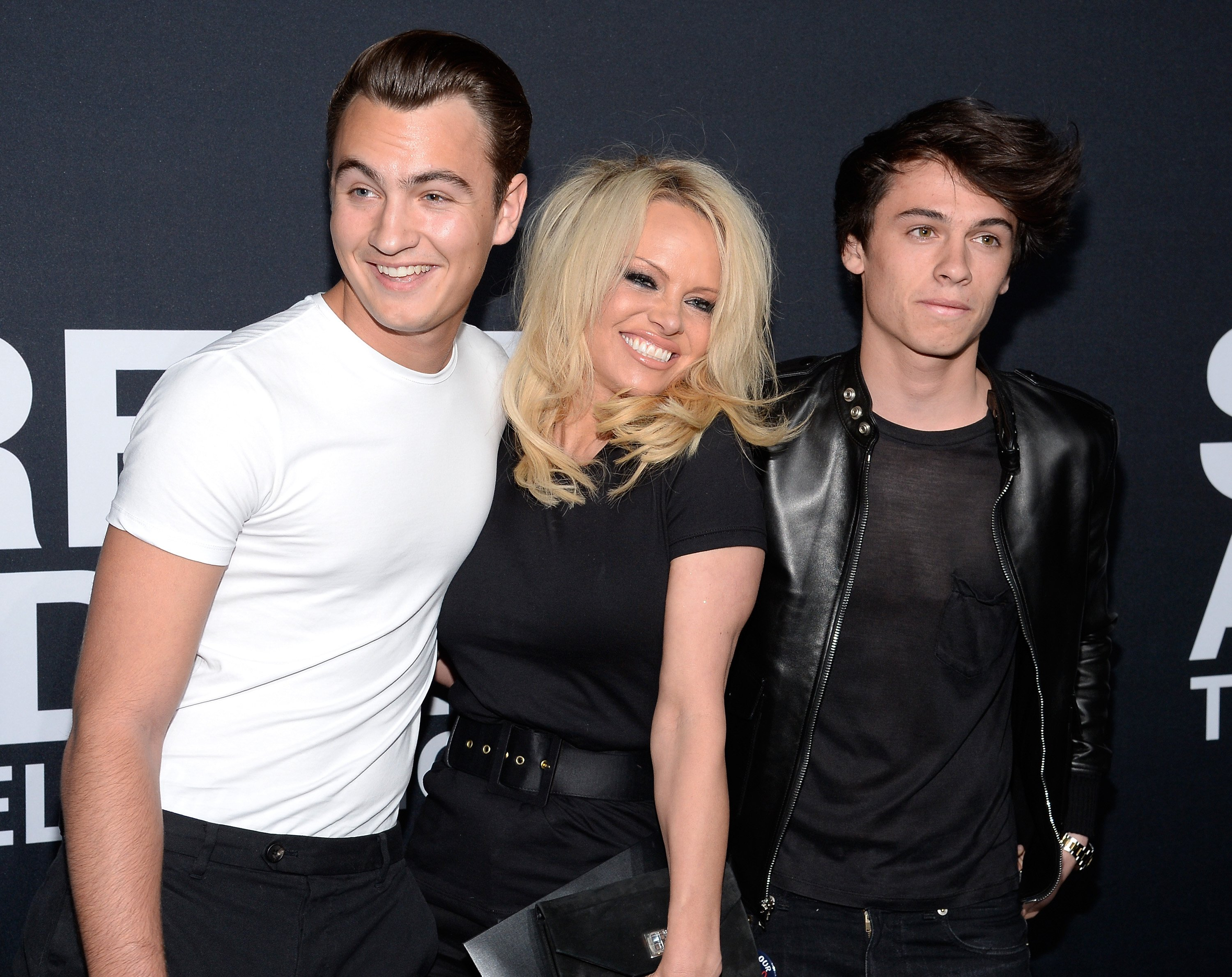 Pamela Anderson (center) and her sons Brandon Lee (L) and Dylan Lee attend the Saint Laurent show at The Hollywood Palladium on February 10, 2016, in Los Angeles, California. | Source: Getty Images.