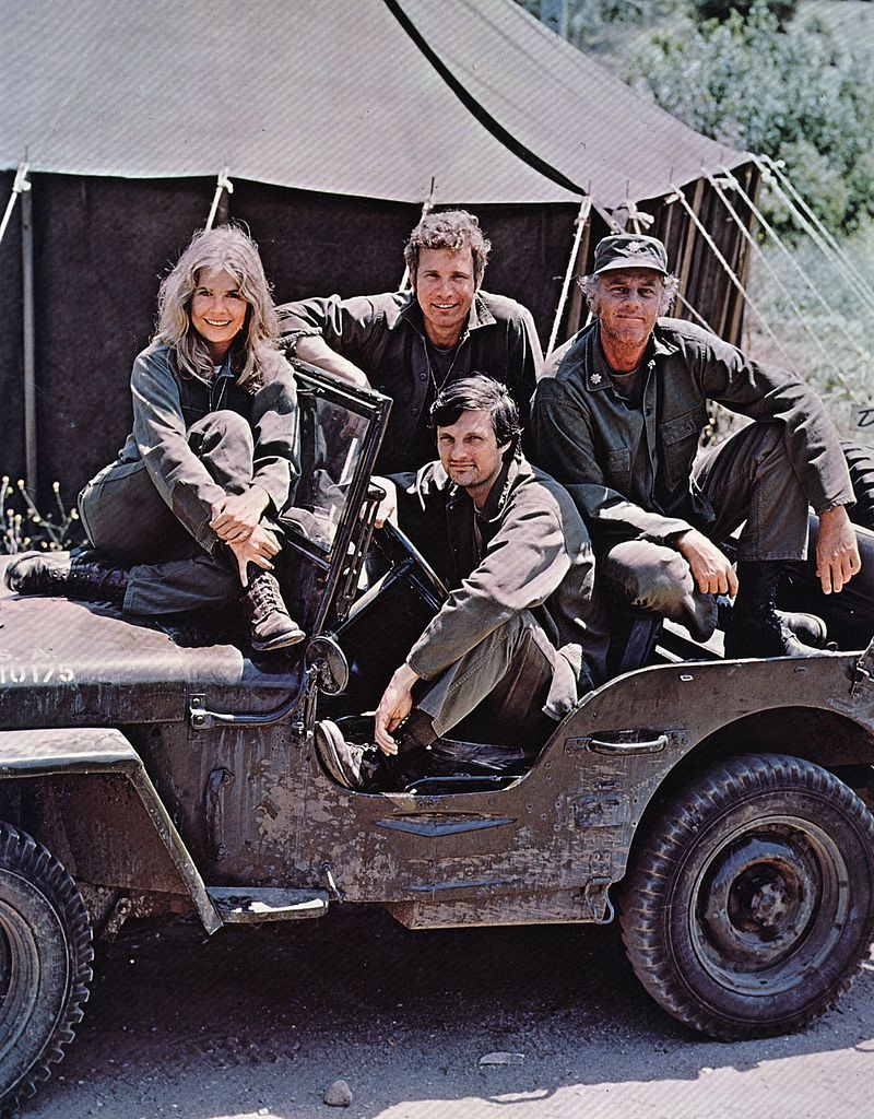 American actor, director and writer Alan Alda in the driving seat of a jeep, surrounded by Loretta Swit and other cast members of the hit television show M.A.S.H, in costume as members of a US Army medical corp. | Getty Images