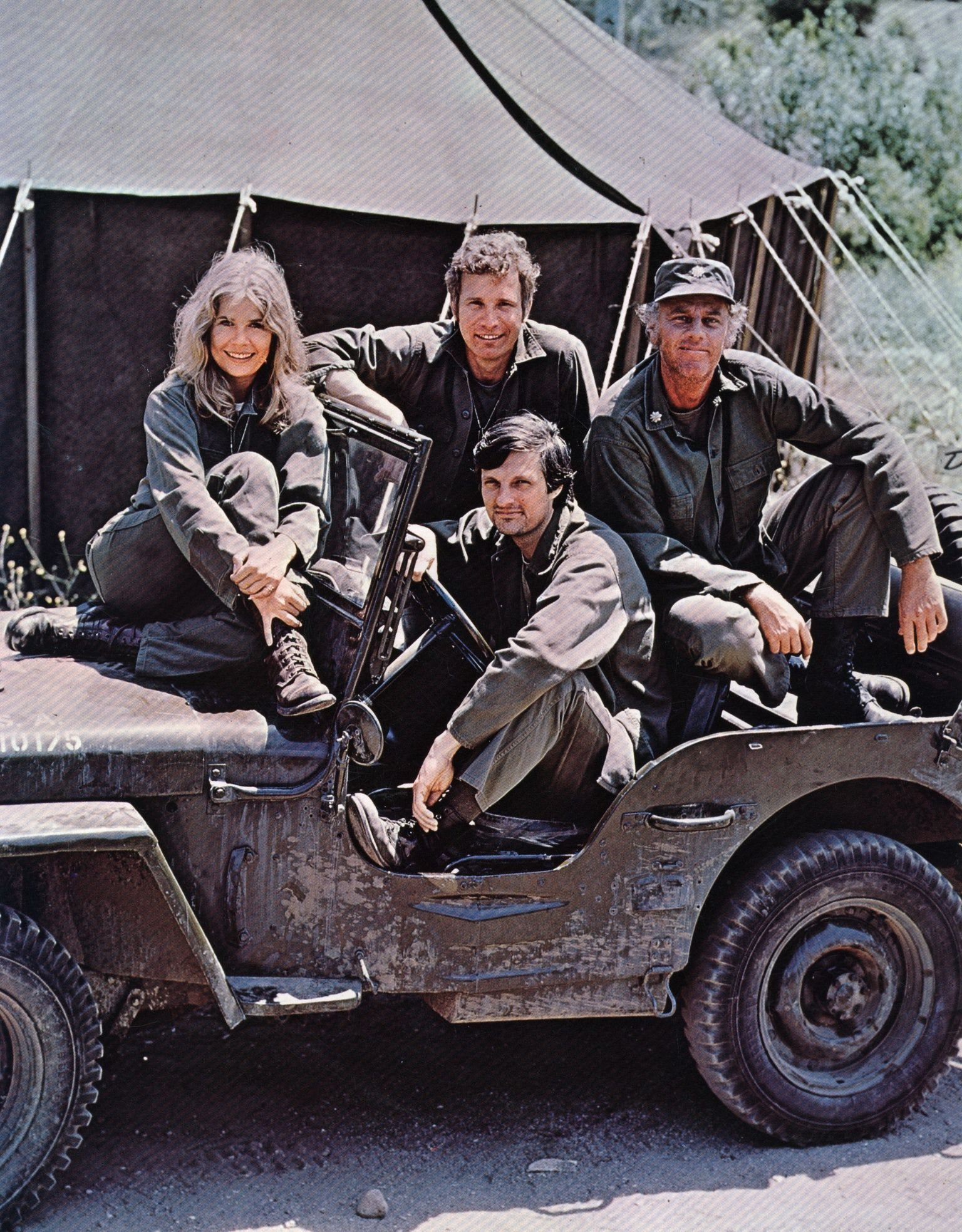 American actor, director and writer Alan Alda in the driving seat of a jeep, surrounded by Loretta Swit and other cast members of the hit television show M.A.S.H | Getty Images