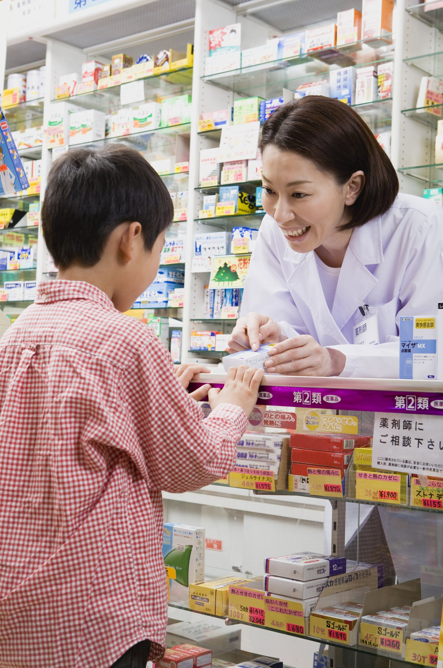 Photo of a pharmacist talking to boy at drugstore | Photo: Getty Images