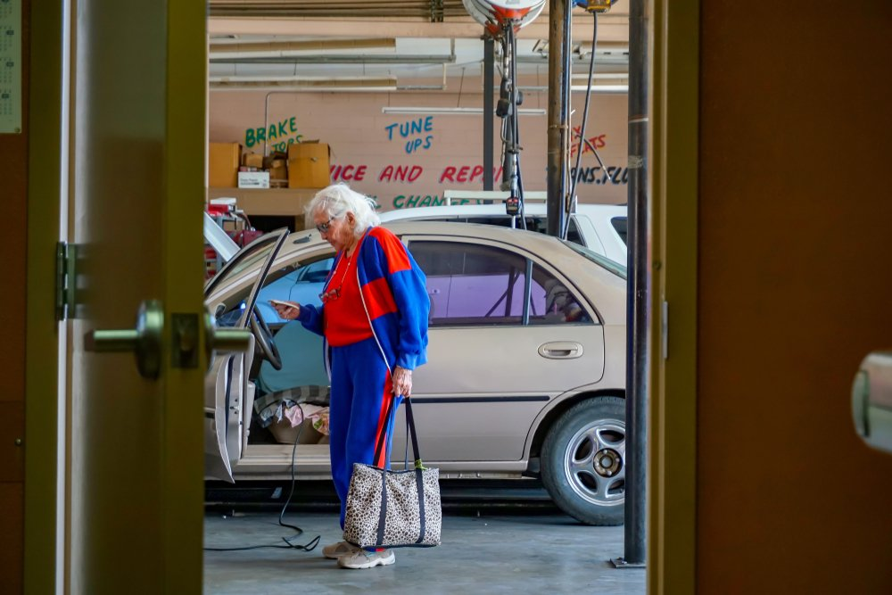 Elderly woman standing near a car in a parking garage | Photo: Shutterstock