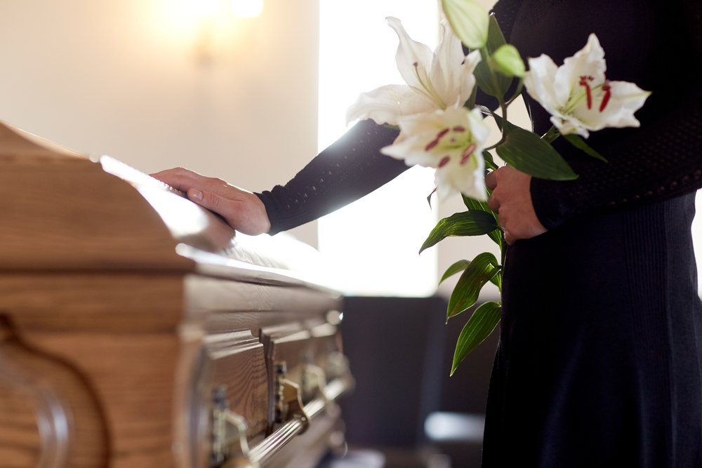 A woman with white lily flowers holding a coffin at a funeral. | Photo: Shutterstock