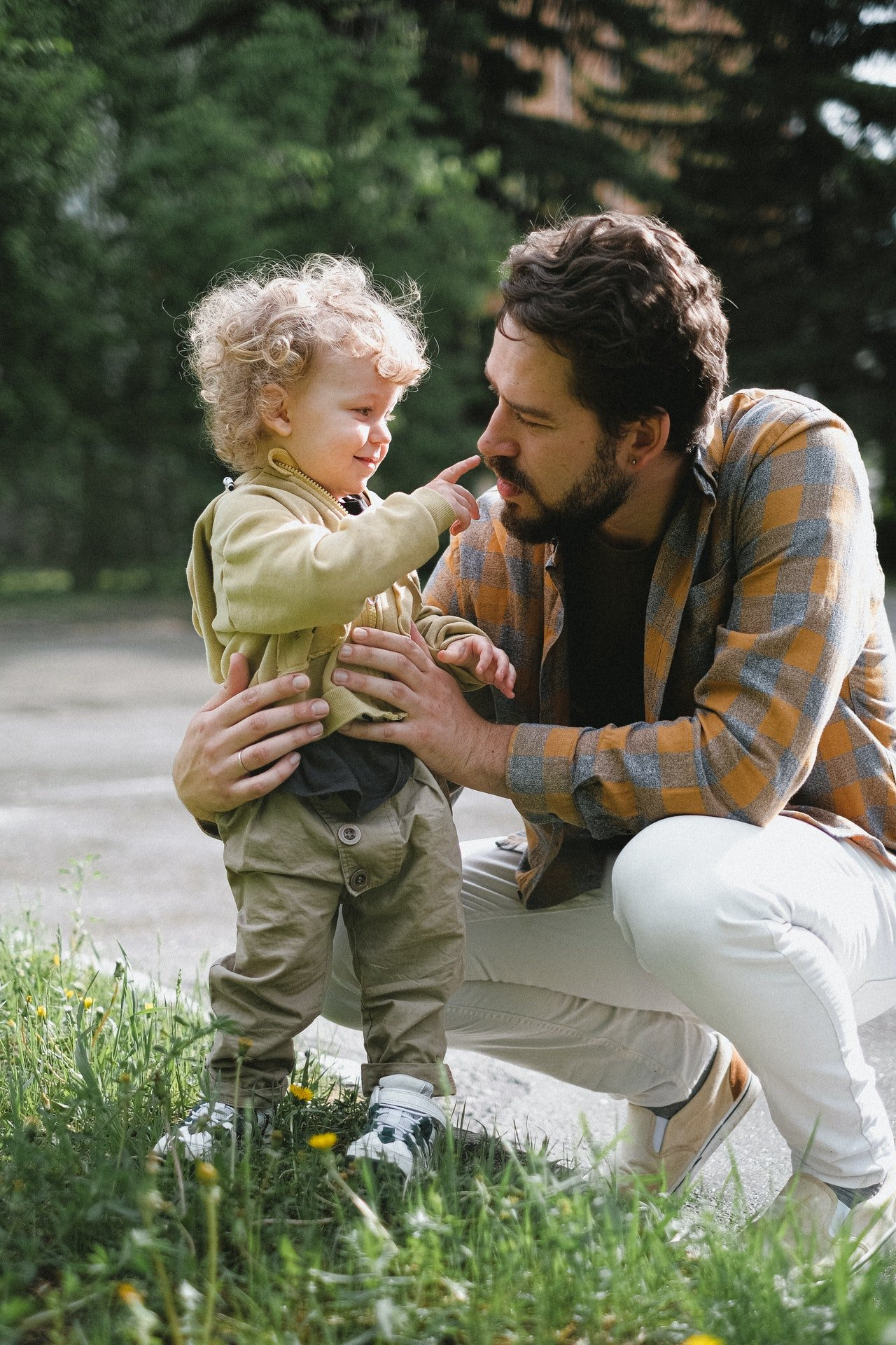 Photo of a father holding his child outside. | Source: Pexels/AnnaShvets