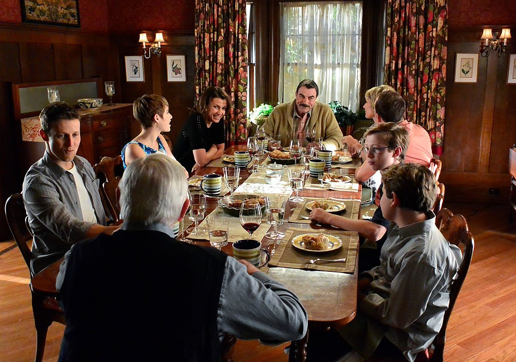 """Tom Selleck, Donnie Wahlberg, Bridget Moynahan, Will Estes, Len Cariou, Amy Carlson, Sami Gayle, Tony Terraciano and Andrew Terraciano at family dinner on """"Blue Bloods."""" Source: Getty Images."""