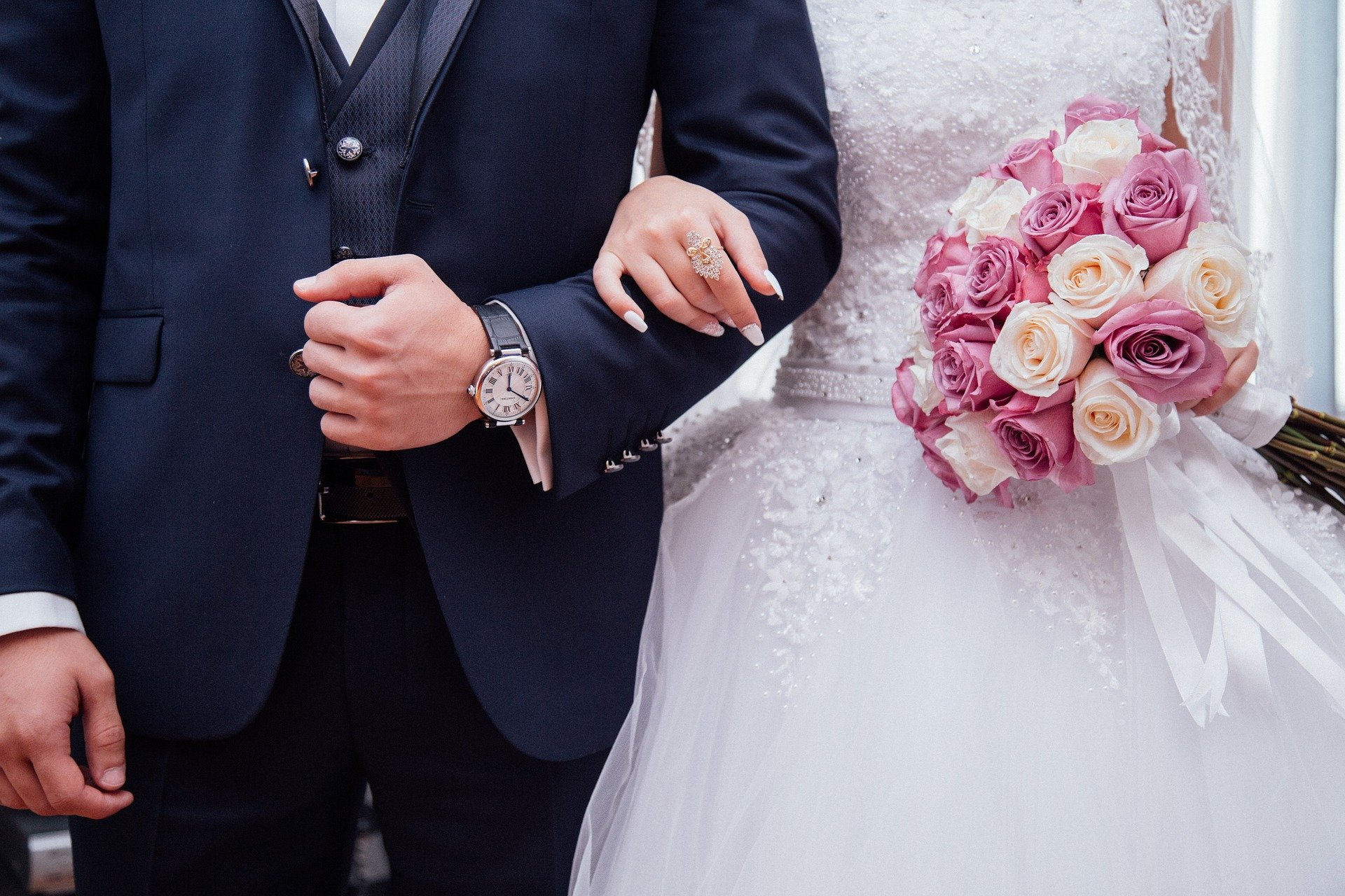 Stock image of midsection of bride and groom with arms linked.   Source: Pixabay