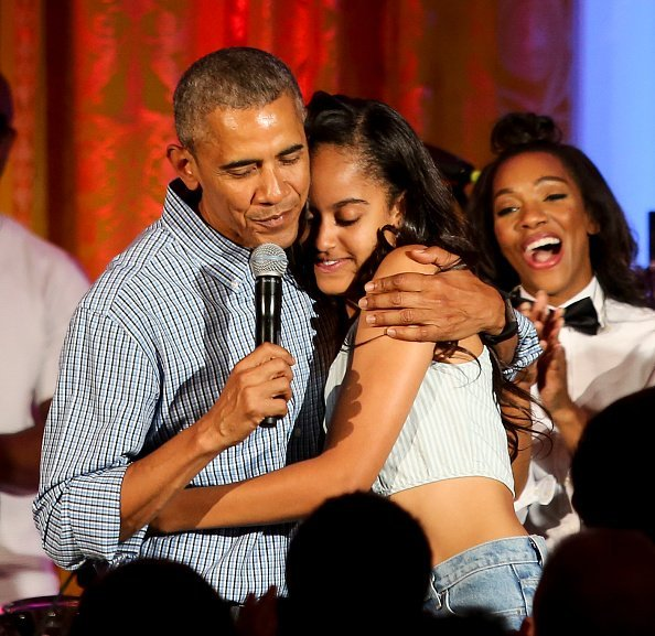 President Barack Obama hugs his daughter Malia at the Fourth of July White House party on July 4, 2016 | Photo: Getty Images