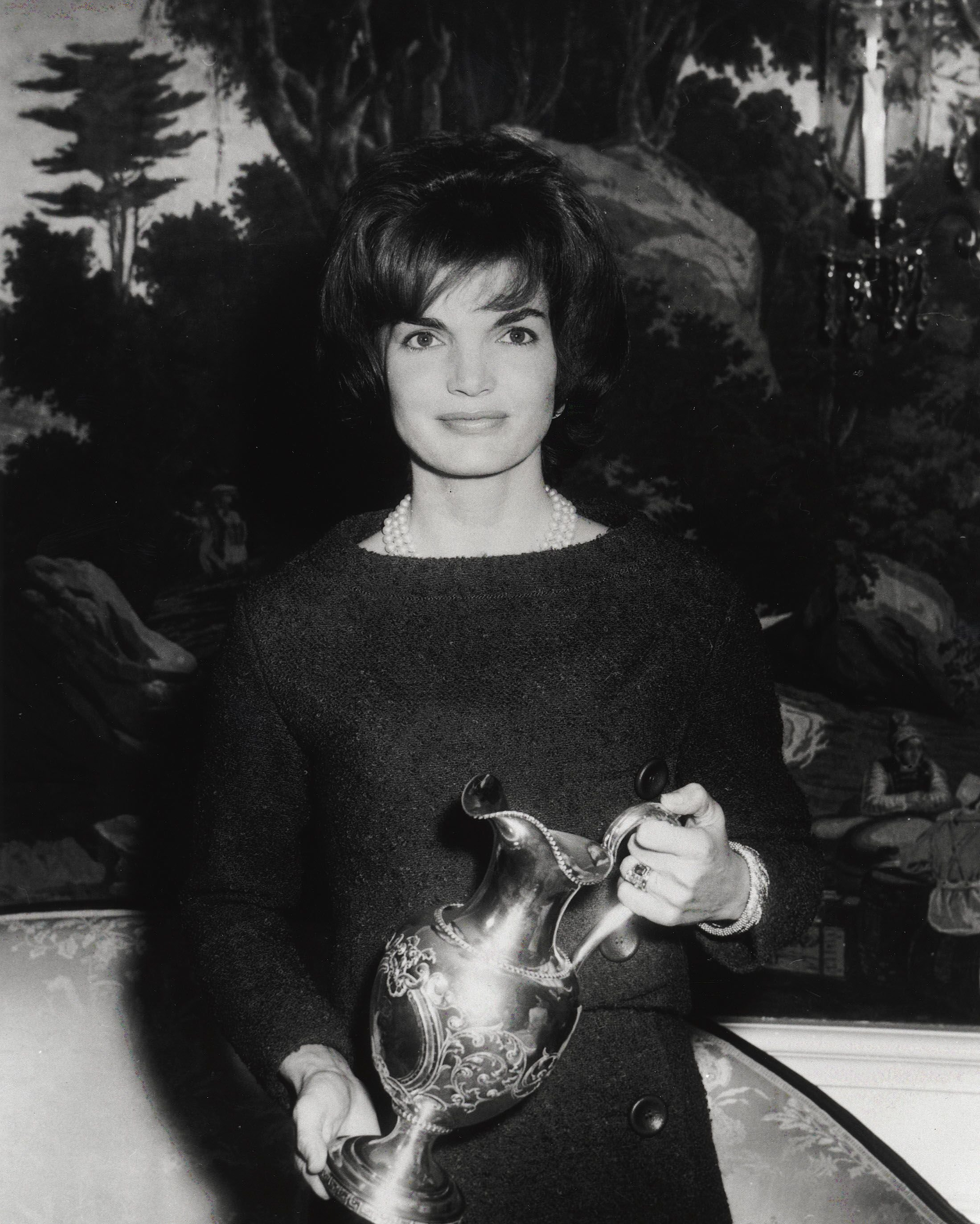 Jacqueline Kennedy poses for a photograph while holding a gift December 12, 1961 at the White House in Washington D.C. | Source: Getty Images
