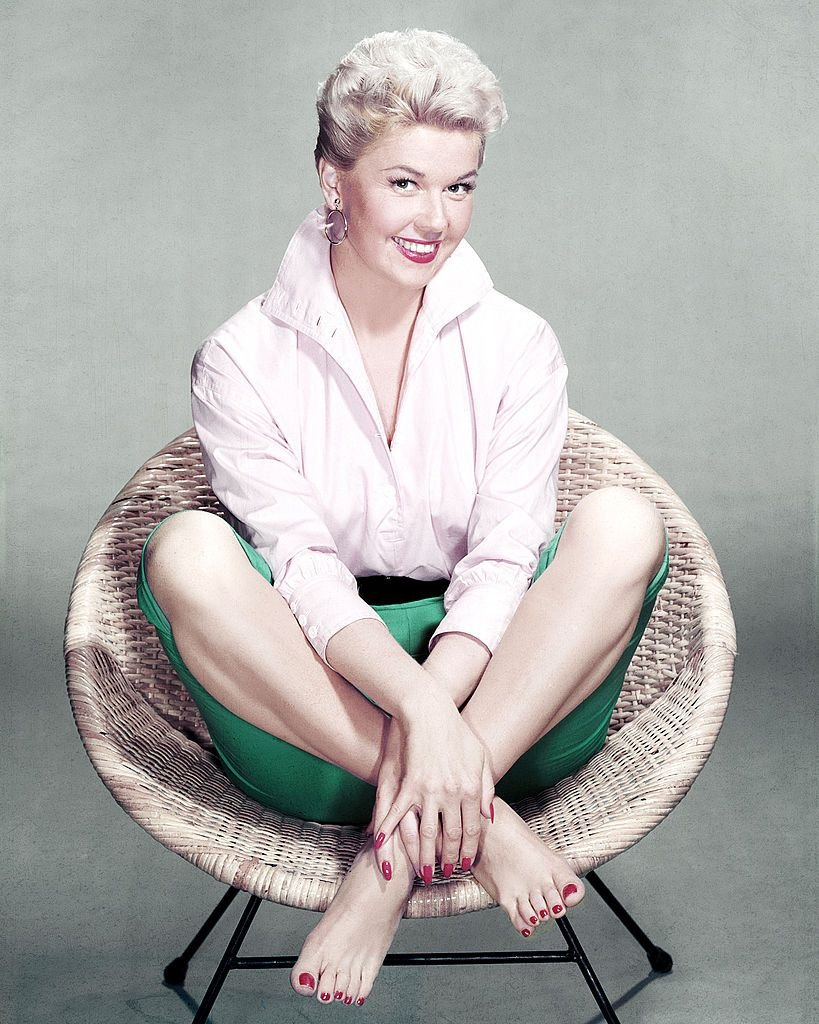 American actress and singer Doris Day sits cross-legged and barefoot in a rattan chair, circa 1955. | Source: Getty Images