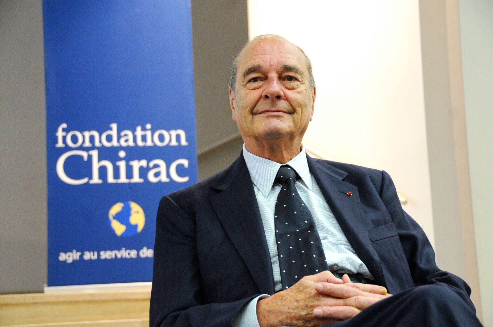 Portrait de Jacques Chirac qui pose devant une affiche de la Fondation Chirac. | Photo : GettyImage