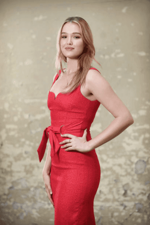 Wearing a red dress, Maddison Brown poses in front of a cement wall during a photo shoot, on September 4, 2019, in Sydney, Australia | Source: Richard Dobson / Newspix via Getty Images
