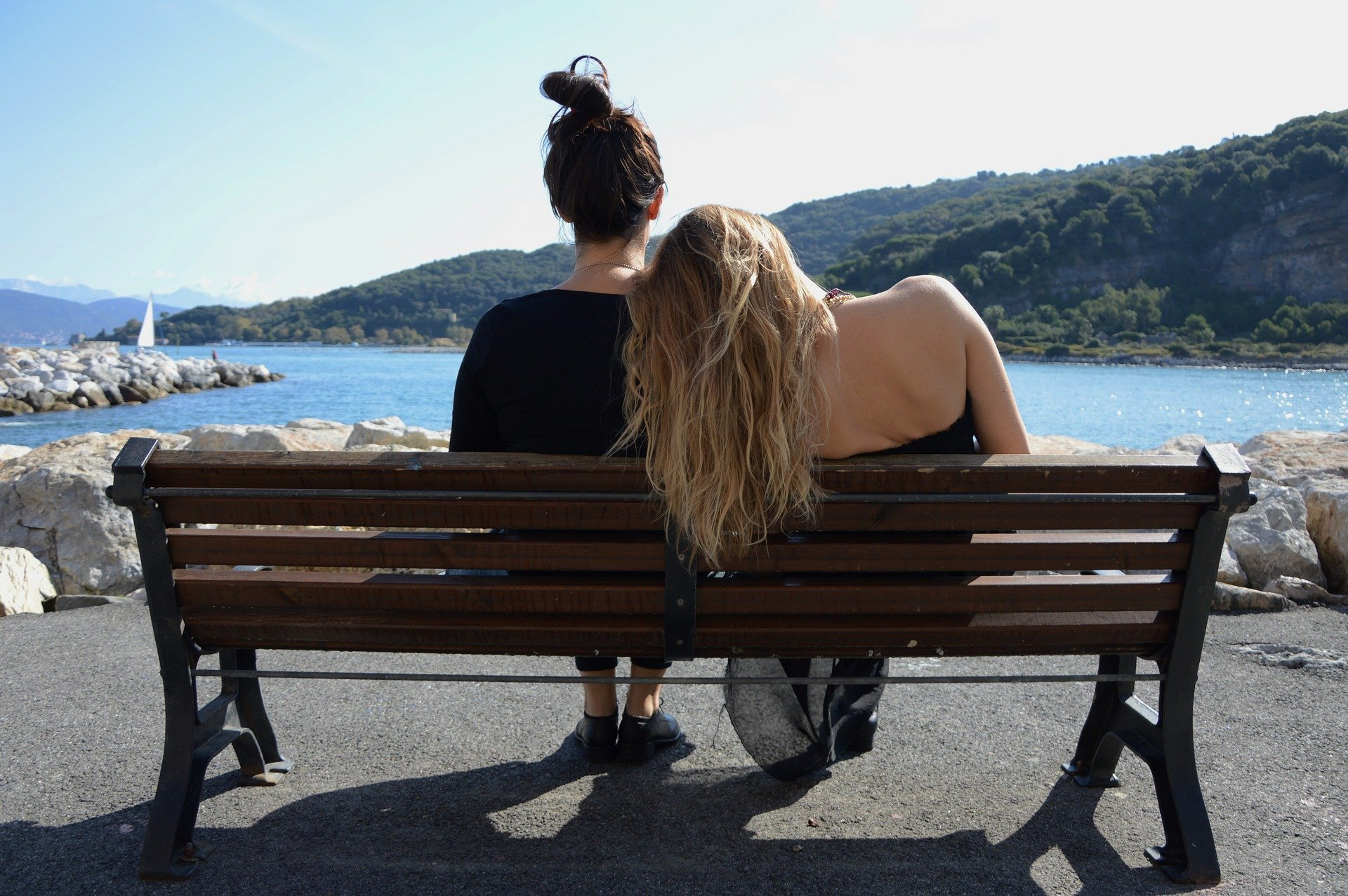 Two sisters sitting on a bench looking at the ocean. | Source: Pixabay.