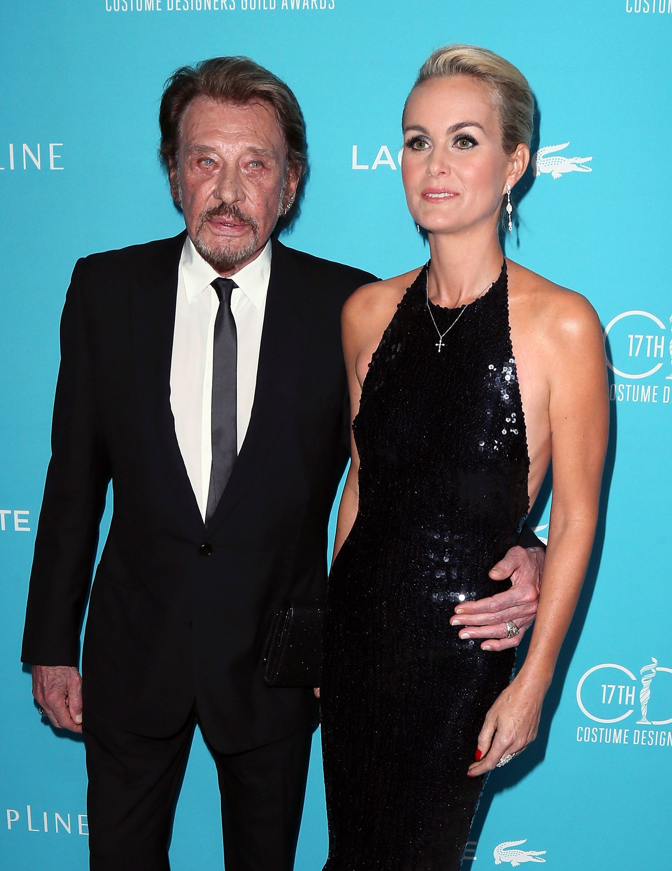 Johnny Hallyday (à gauche) et son épouse Laeticia Hallyday assistent à la 17e remise des Costume Designers Guild Awards à l'hôtel Beverly Hilton à Beverly Hills, Californie. | Photo : Getty Images