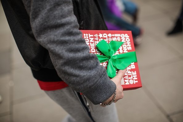 A man carries a gift-wrapped box on Oxford Street in London, England | Photo: Getty Images