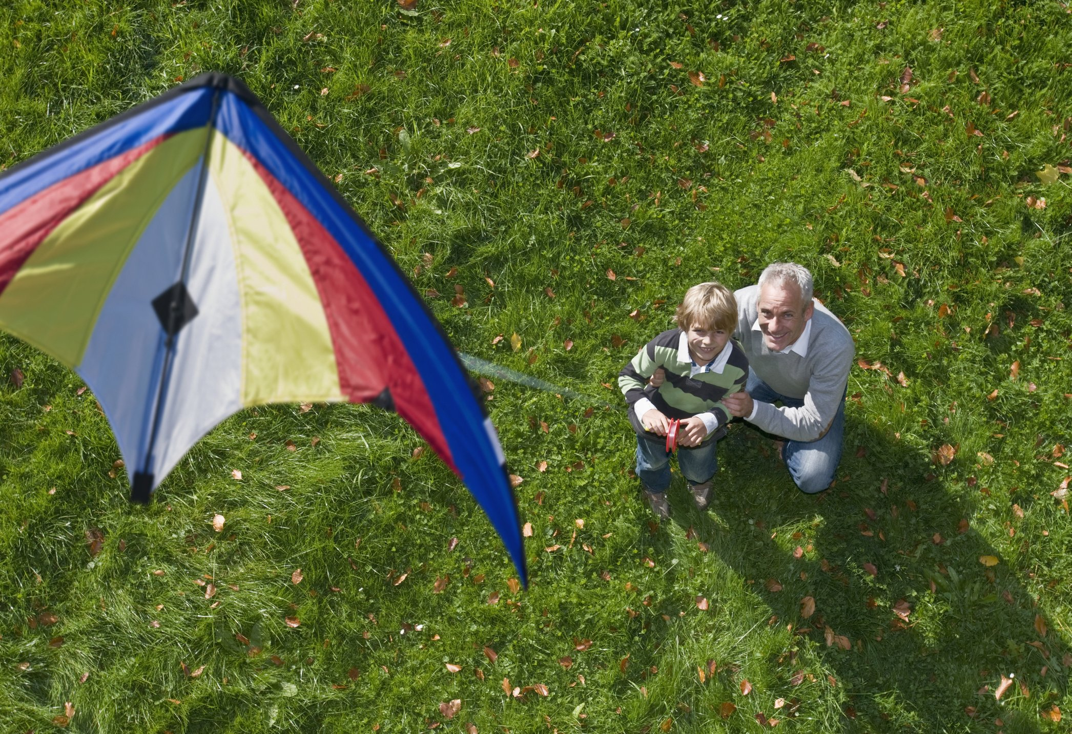 A father and a son pictured flying a kite from above.   Photo: Getty Images