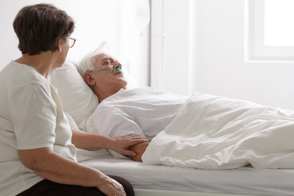Senior man in a coma laying on hospital bed and his wife sitting next to him. | Photo: Shutterstock
