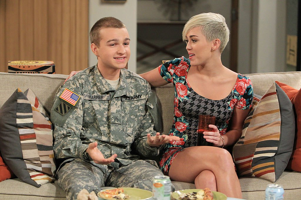 Jake (Angus T. Jones, left) and Missi (Miley Cyrus, right) plan a rendezvous at the beach house, on TWO AND A HALF MEN, Thursday, Nov. 8, 2012.   Source: Getty Images