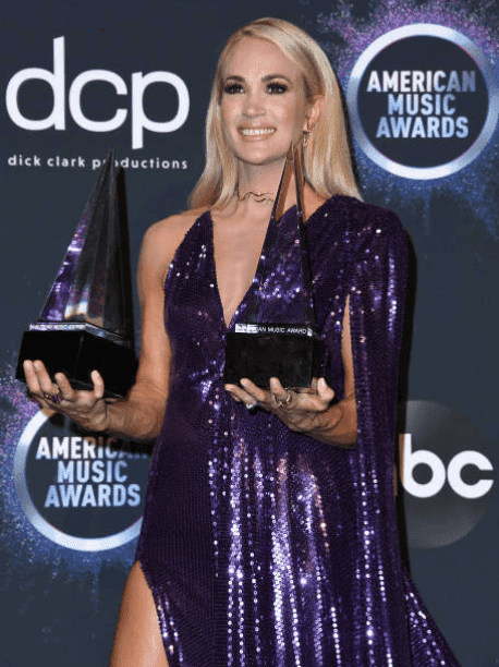 Carrie Underwood holds up two of her awards at the 2019 American Music Awards on November 24, 2019m in Los Angeles, California| Source: Getty Images (Photo by Steve Granitz/WireImage)
