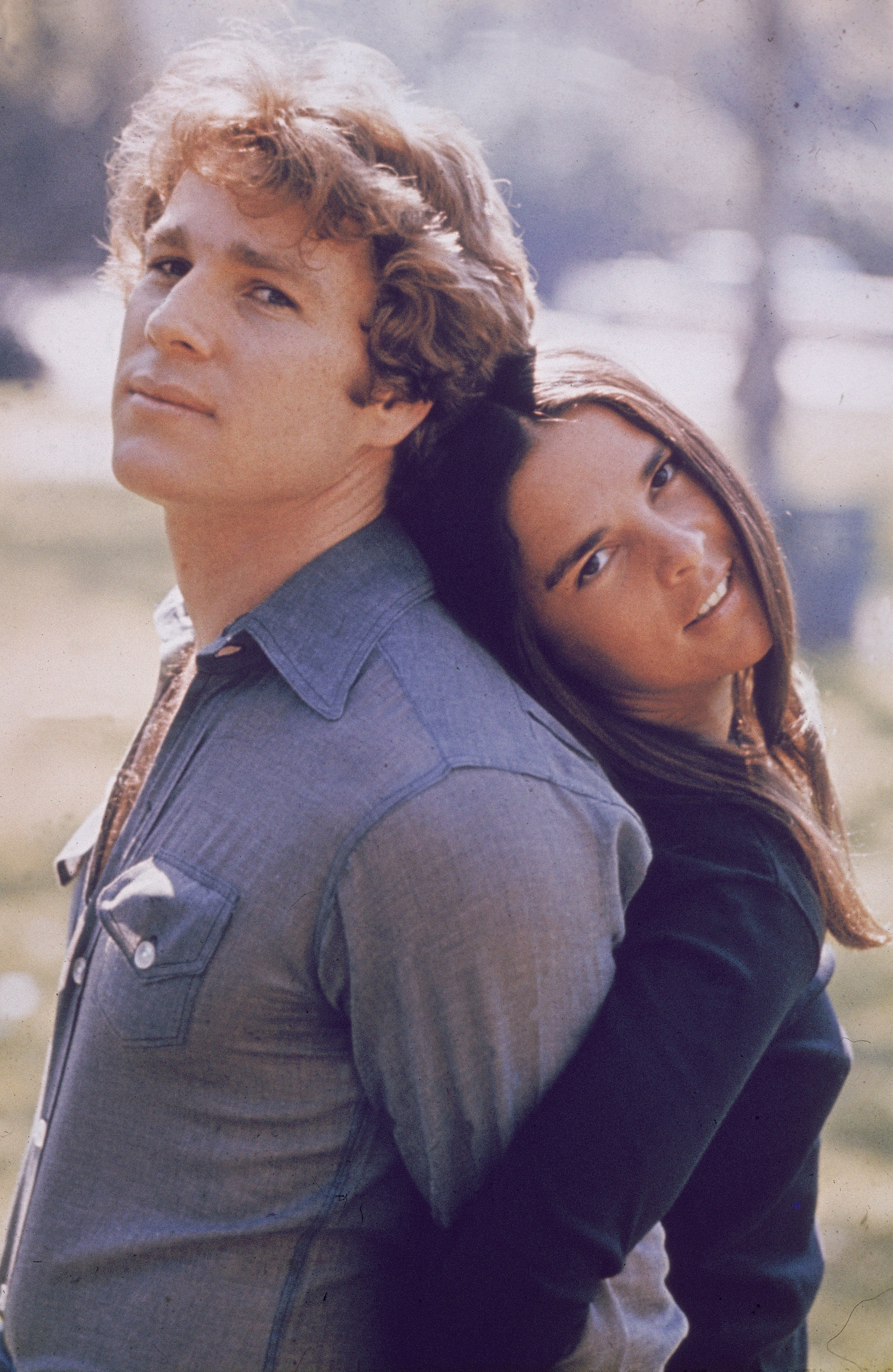 """Ryan O'Neal and Ali MacGraw stand back to back outdoors in a still from the film, """"Love Story,"""" circa 1970   Photo: Getty Images"""