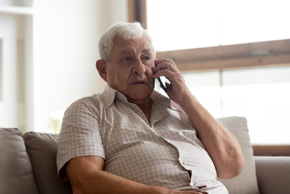 Elderly man in casual clothes seated on couch in living room making a phone call. | Photo: Shuterstock.