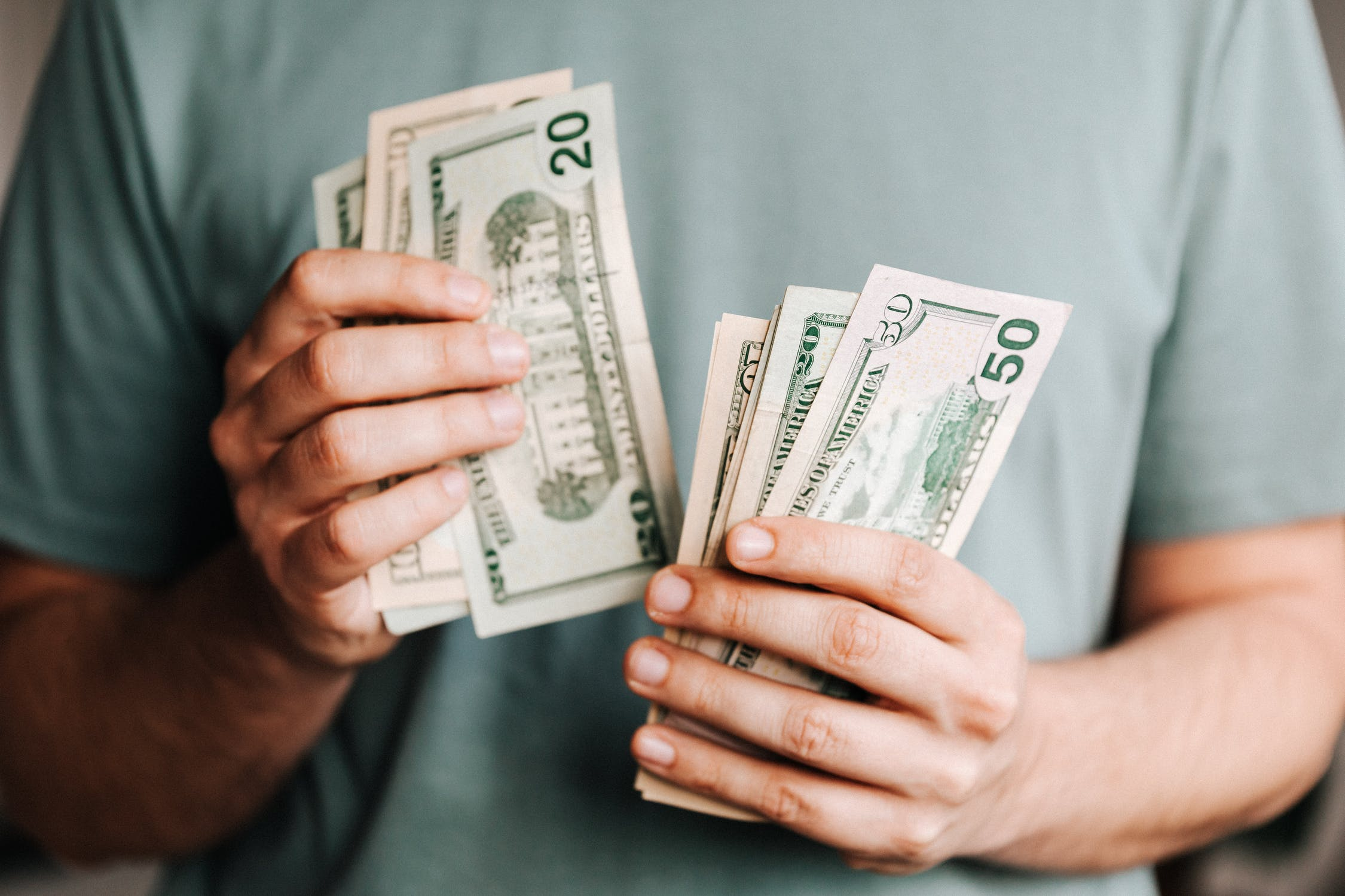The young man with a handful of money   Source: Pixabay