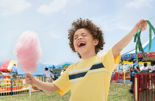 Photo of a young boy with cotton candy and prize tickets at fair  | Photo: Getty Images
